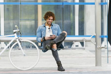 Handsome young man with mobile phone and fixed gear bicycle in the street.
