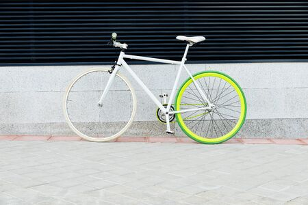 City bicycle fixed gear on wall. Cycling or commuting in city urban environment, ecological transportation concept.