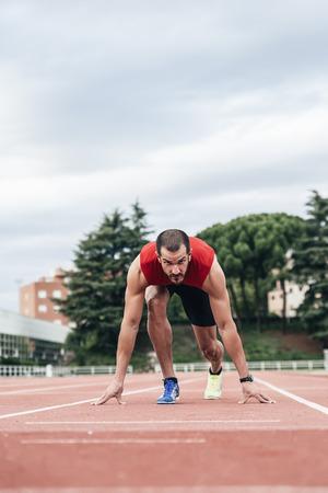 Man getting ready to start running on Stadium Stock Photo