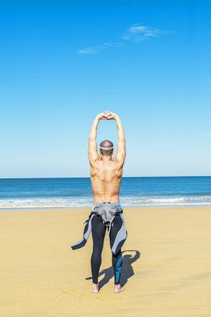 scuba goggles: fitness man swimmer training stretching on the beach Stock Photo