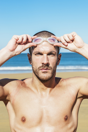 handsome swimmer putting on goggles on the beach