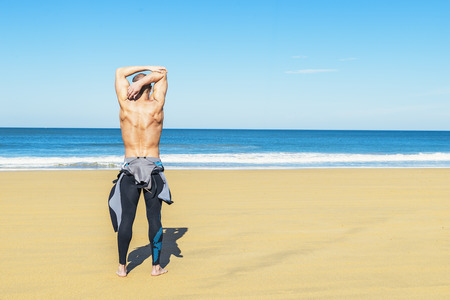 fitness man swimmer training stretching on the beach Stock Photo