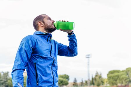 Handsome runner after run resting and drinking water on bottle Stock Photo