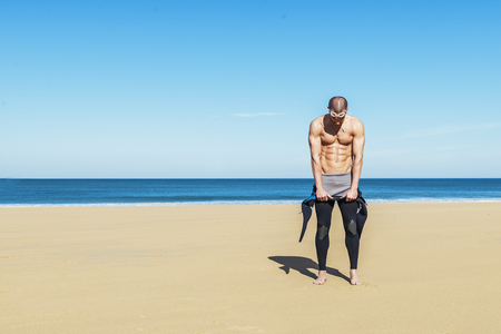 scuba goggles: swimmer putting on his wetsuit on the beach Stock Photo