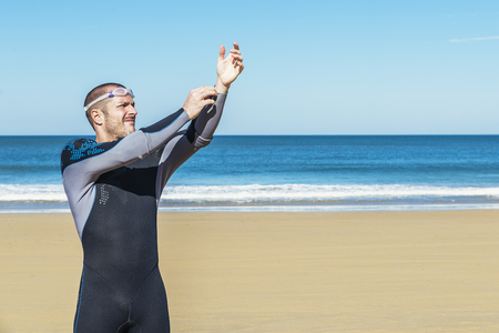 swimmer putting on his wetsuit on the beach Stock Photo
