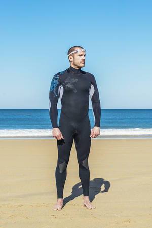 Handsome Swimmer ready to start swimming on the beach Stock Photo