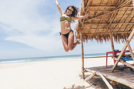 Woman Jumping On The Beach. Holidays Concept.