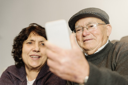 Senior rmarriage using his mobile phone at home.