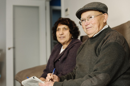 Elderly couple reading a newspaper sitting on the sofa at home. Stock Photo