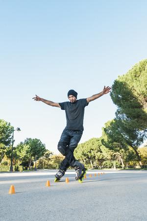 Stedelijke jonge man op rolschaatsen op de weg in de zomertijd. roller Concept