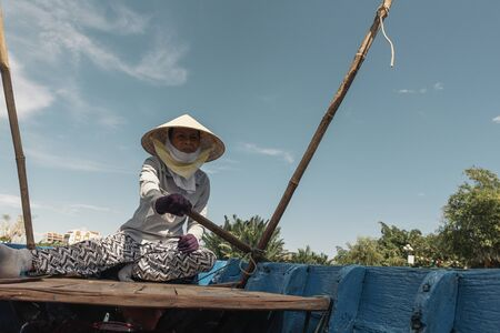 Vietnamese Woman on a Boat Rowing. Vietnam Concept. Stock Photo