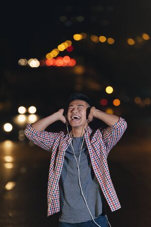 Portrait of a asian young man listening music with headphones in the city. Stock Photo