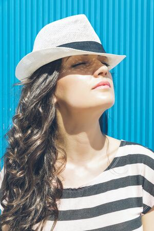 pretty brunette woman: Attractive elegant summer woman portrait with hat on the blue wall Stock Photo