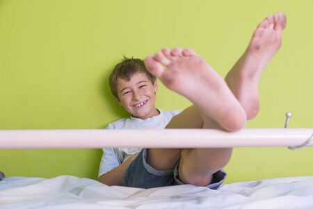 pieds sales: Little kid smiling with dirty feet and sitting at bed, posing on green background close-up Banque d'images