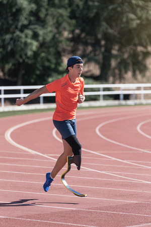 Disabled man athlete training with leg prosthesis. Paralympic Sport Concept.