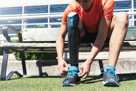 Gehandicapte man atleet klaar voor training met beenprothese. Paralympische sportconcept.