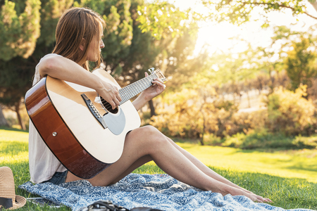 Beautiful woman playing guitar in the park.