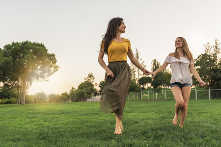 Beautiful women smiling and having fun and running in the park. Friends and summer concept.