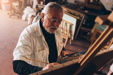 Old man artist painting oils in his studio. Artist Concept. Фото со стока