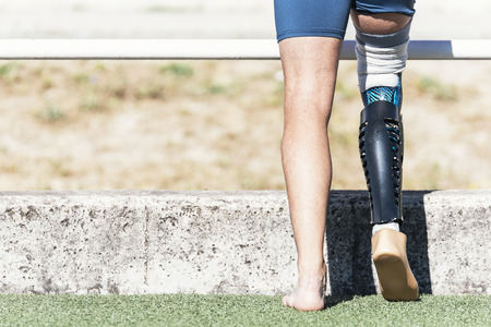 Close up disabled man athlete with leg prosthesis. Paralympic Sport Concept. Standard-Bild