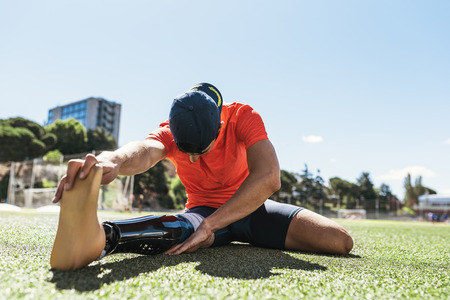 Gehandicapte man atleet die zich uitstrekt met beenprothese. Paralympische Sport Concept.
