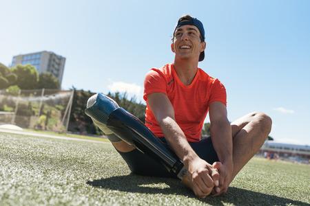 Behinderter Mannathlet, der mit Beinprothese ausdehnt. Paralympisches Sportkonzept. Standard-Bild