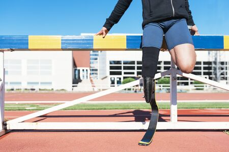 Disabled man athlete stretching with leg prosthesis Stock Photo