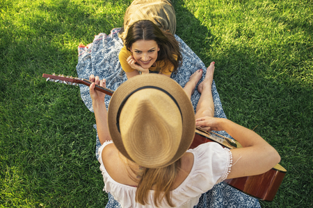 Beautiful women having fun playing guitar in the park. Friends and summer concept.