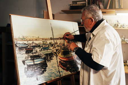 Old man artist painting oils in his studio. Artist Concept. Reklamní fotografie - 83585031