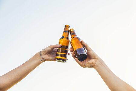 Female friends cheers clinking bottles of beer in hands. 写真素材