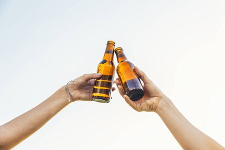 Female friends cheers clinking bottles of beer in hands. Stockfoto