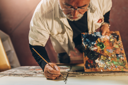 Old man artist painting oils in his studio. Artist Concept. Standard-Bild