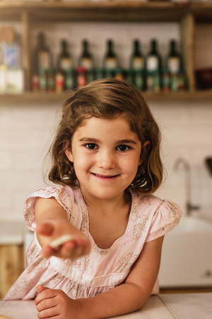 Little girl showing her cookie. Infant Chef Concept.