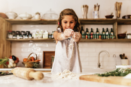 Little child girl kneading dough prepare for baking cookies. Infant Chef Concept.