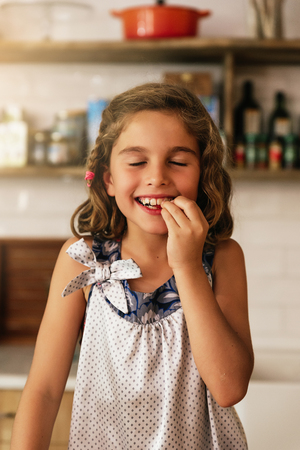 Little girl eating chocolate while preparing baking cookies. Infant Chef Concept. Stock Photo