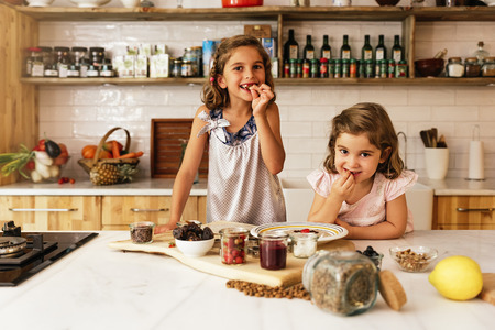Little sisters girl preparing baking cookies. Infant Chef Concept.