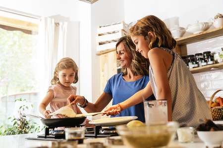 Little sisters cooking with her mother in the kitchen. Infant Chef Concept. Standard-Bild