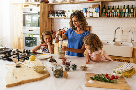 Irmãs pequenas cozinhando com sua mãe na cozinha. Conceito de cozinheiro infantil. Foto de archivo - 83847254