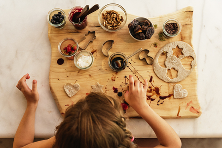 Top view of little girl preparing baking cookies. Infant Chef Concept.