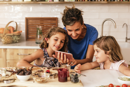 Little sisters cooking with her mother in the kitchen. Infant Chef Concept. Stock Photo