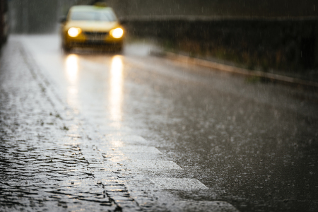 Taxi circulating on wet asphalt while its raining. Rain Concept. Stock Photo