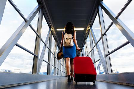 Młoda dziewczyna podróżnik chodzenie z prowadzeniem przytrzymaj walizkę na lotnisku. Koncepcja turystyczna. Zdjęcie Seryjne