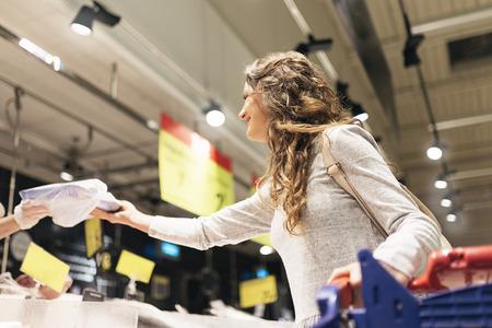 スーパーで魚を買う美しい女性。マーケットフードコンセプト。
