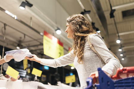 Beautiful woman buying fish in supermarket. Market food Concept.