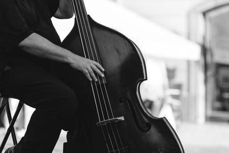 거리에서 더블베이스를 연주하는 음악가. 악기 개념.