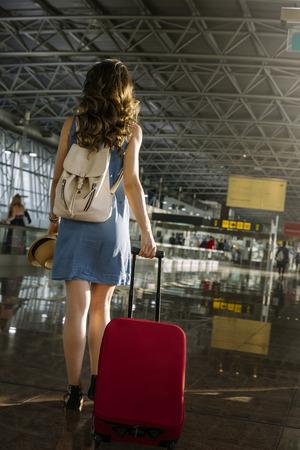 空港でスーツケースを持ち歩く若い女の子の旅行者。観光コンセプト。