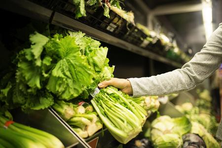 Ciérrese para arriba de la mujer que toma una lechuga en supermercado. Concepto de comida de mercado.