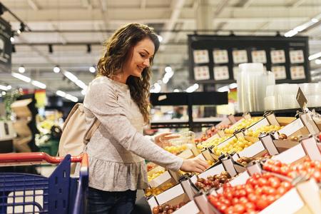 Hermosa mujer tomando alimentos en el supermercado. Concepto de comida de mercado.