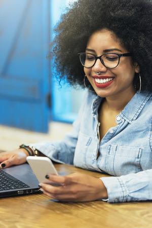Het mooie afro Amerikaanse vrouw mobiel gebruiken en laptop in de koffiewinkel. Communicatie concept.