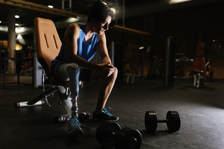 Portrait of disabled young man in the gym. Disabled Sportsman Concept. Stock Photo